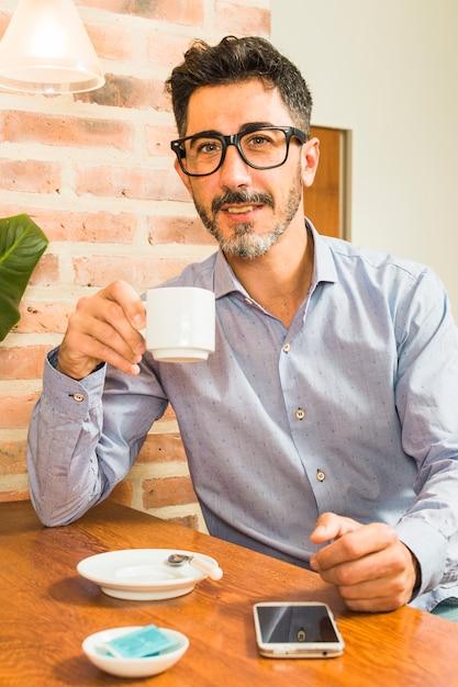 Porträt eines mannes, der in der hand kaffeetasse mit handy auf tabelle hält Kostenlose Fotos