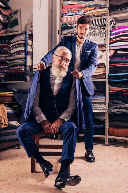 Porträt eines mannes, der mantel über der schulter seines älteren mannes hält Kostenlose Fotos