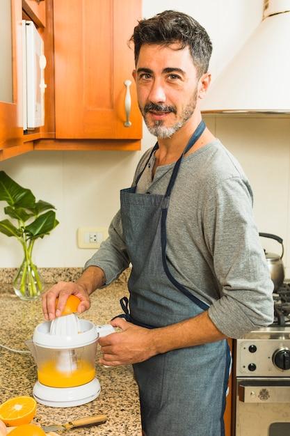 Porträt eines mannes, der orangensaft in der küche macht Kostenlose Fotos