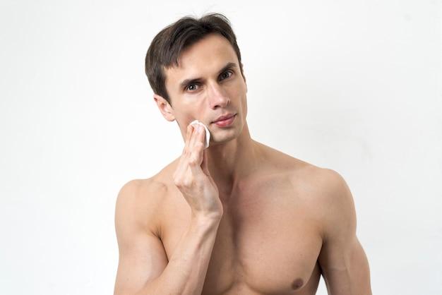 Porträt eines mannes, der sein gesicht säubert Kostenlose Fotos