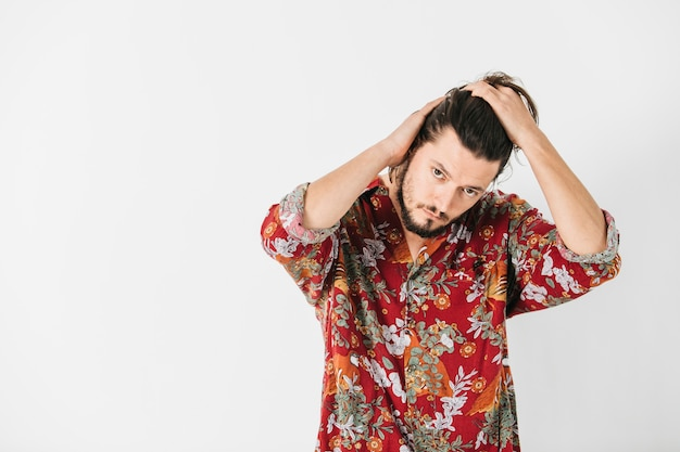 Porträt eines mannes, der sein haar mit den händen lokalisiert auf weißem hintergrund pflegt Kostenlose Fotos