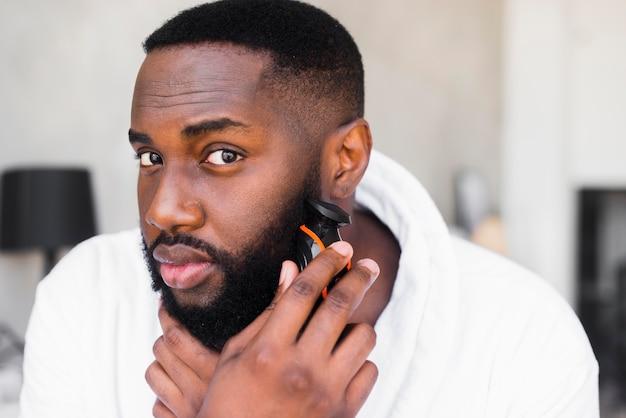 Porträt eines mannes, der seinen bart rasiert Premium Fotos
