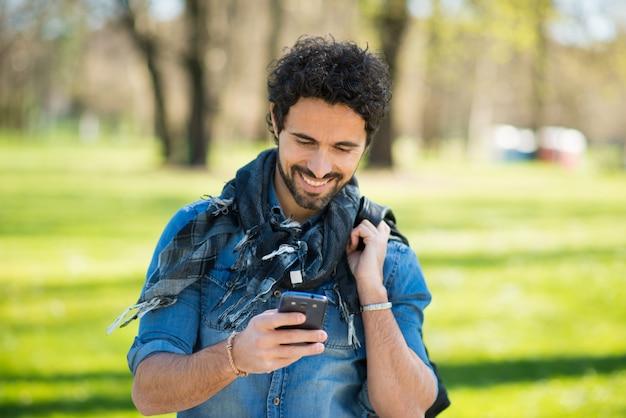 Porträt eines mannes, der seinen handy in einem park verwendet Premium Fotos