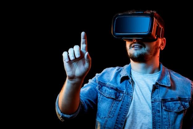 Porträt eines mannes in den gläsern der virtuellen realität, vr, gegen einen dunklen hintergrund. Premium Fotos
