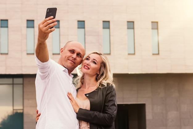 Porträt eines mannes und einer frau lächelnd, während selfie in der stadt nehmen Premium Fotos