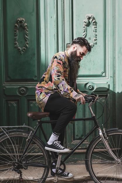 Porträt eines modernen jungen mannes, der fahrrad fährt Kostenlose Fotos