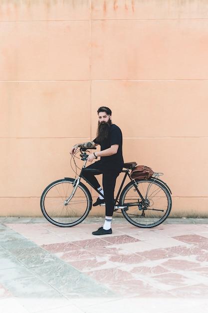 Porträt eines modernen mannes, der mit seinem fahrrad gegen wand steht Kostenlose Fotos