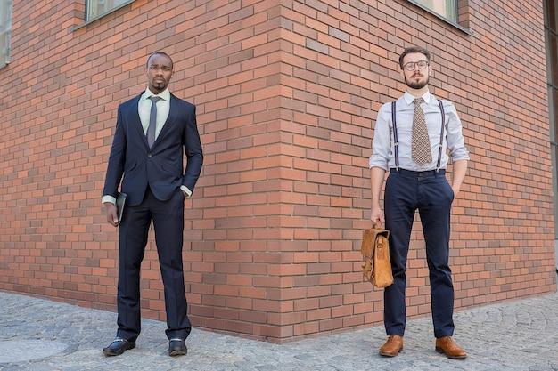 Porträt eines multiethnischen geschäftsteams. zwei männer stehen vor dem hintergrund der stadt. der eine mann ist afroamerikaner, der andere ist europäer. konzept des geschäftserfolgs Kostenlose Fotos