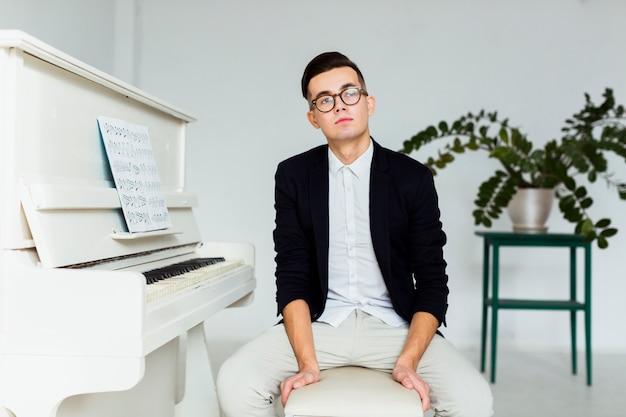 Porträt eines nachdenklichen jungen mannes, der nahe dem klavier sitzt Kostenlose Fotos