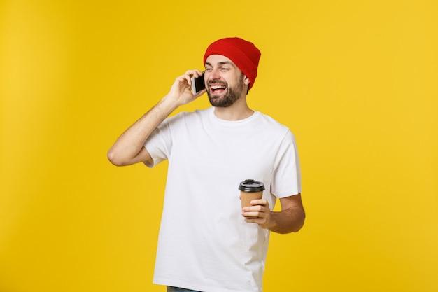 Porträt eines netten jungen mannes, der die zufällige kleidung steht lokalisiert trägt und hält den handy und trinkt mitnehmerkaffee. Premium Fotos