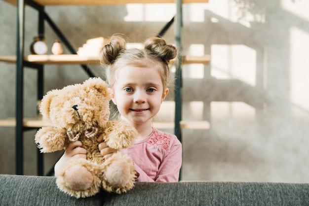 Porträt eines netten kleinen mädchens, das mit teddybären steht Kostenlose Fotos