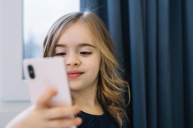 Porträt eines netten mädchens, das selfie mit handy nimmt Kostenlose Fotos