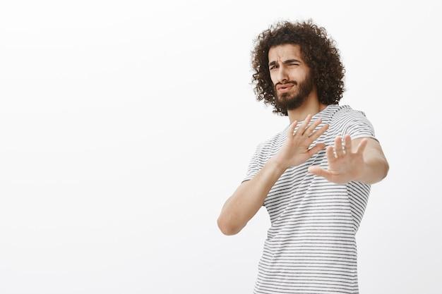 Porträt eines niedlichen bärtigen verdauten mannes im trendigen outfit, der sich nach hinten beugt und die handflächen nach vorne zieht, sich gegen etwas schreckliches verteidigt, antipathie und abneigung ausdrückt Kostenlose Fotos