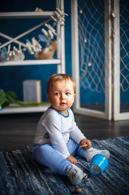 Porträt eines niedlichen kleinen jungen im innenraum mit seestil Premium Fotos