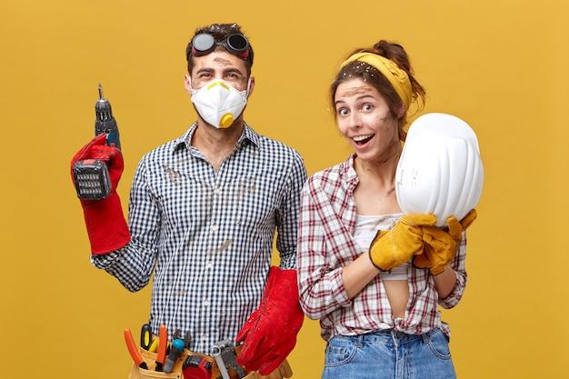 Porträt eines positiven mannes mit bohrmaschine und werkzeuggürtel und seiner kollegin, die helm mit herrlichem ausdruck hält Kostenlose Fotos