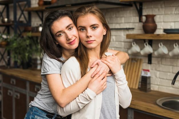 Porträt eines reizenden lesbischen jungen paares, das in der küche steht Kostenlose Fotos