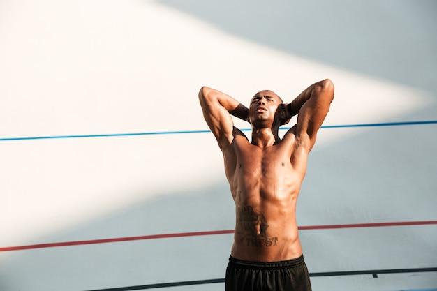 Porträt eines schönen afrikanischen läufers, der nach lauf auf stadion ruht Kostenlose Fotos
