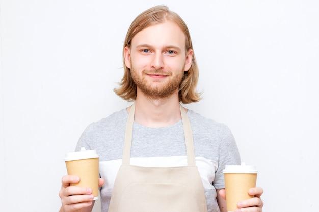 Porträt eines schönen barista im grauen t-shirt und in der schürze, die zwei pappbecher halten. hipster barista mann mit langer frisur und bart Premium Fotos