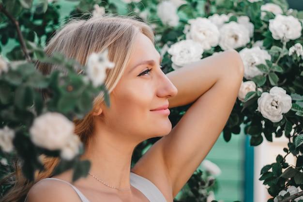 Porträt eines schönen blonden mädchens mit frisur eines busches der weißen rosen. hochzeitsfotosession Premium Fotos