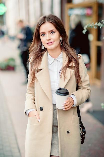 Porträt eines schönen brunettemädchens, das entlang die straße geht. einweggeschirr zum mitnehmen in einer hand halten. lächelt. städtische szene der stadt. warmes sonniges herbstwetter. auf der strasse Premium Fotos