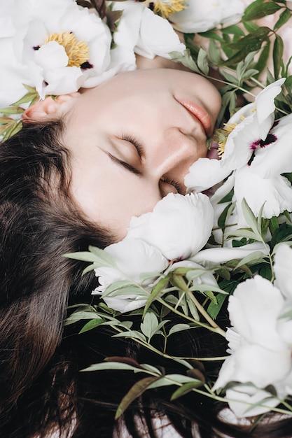 Porträt eines schönen brunettemädchens mit den weißen und purpurroten blumen. junges mädchen des schönen brunette, das blumen genießt. cover-ideenstimmung Premium Fotos
