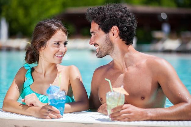 Porträt eines schönen jungen paares, das ein cocktail auf dem poolside genießt Premium Fotos