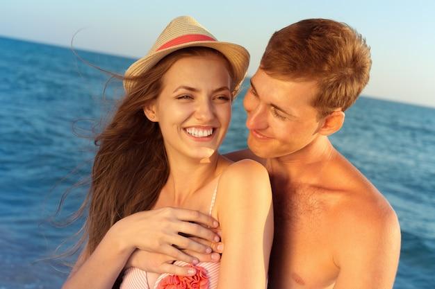 Porträt eines schönen liebevollen paares, das spaß am strand hat Premium Fotos