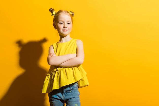 Porträt eines schönen mädchens in einer gelben bluse und in blue jeans. Premium Fotos