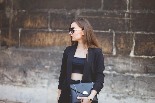 Porträt eines schönen mädchens mit sonnenbrille und eine tasche in seinen händen auf dem hintergrund einer steinmauer Premium Fotos