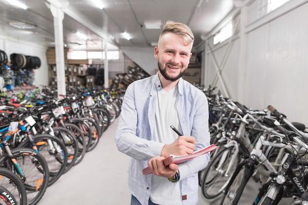 Porträt eines schreibens des glücklichen mannes auf dokument im fahrradshop Kostenlose Fotos