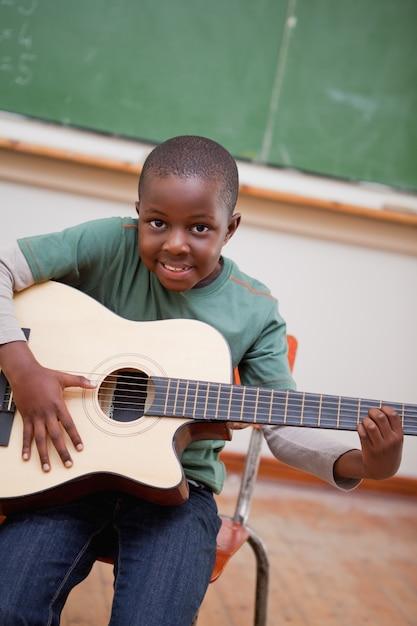 Porträt eines schülers, der die gitarre spielt Premium Fotos