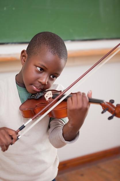 Porträt eines schülers, der die violine spielt Premium Fotos