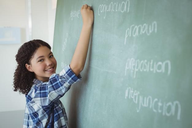 Porträt eines schulmädchens, das vorgibt, lehrerin im klassenzimmer zu sein Premium Fotos