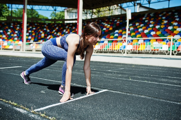 Porträt eines starken sitzmädchens in der sportkleidung, die in das stadion läuft. Premium Fotos