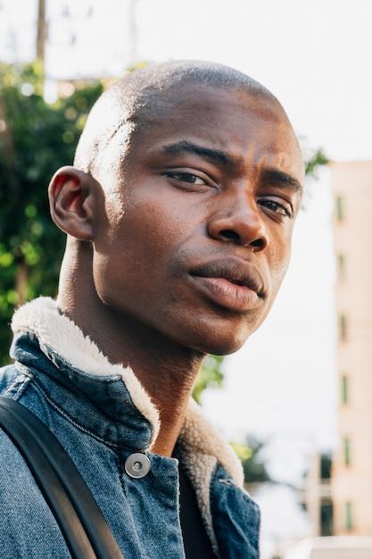 Porträt eines stilvollen rasierten afrikanischen jungen mannes, der kamera betrachtet Kostenlose Fotos