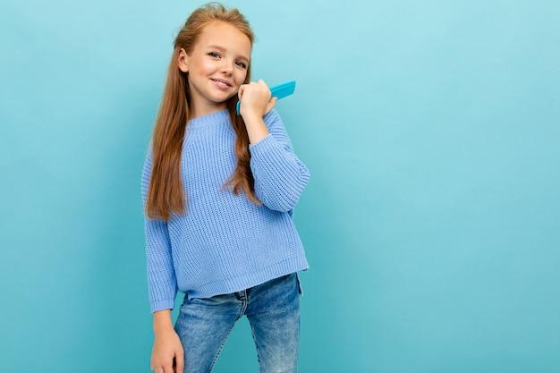 Porträt eines stilvollen schönen reizend schulmädchens in einer blauen strickjacke mit einer haarbürste auf einem hintergrund der blauen wand Premium Fotos