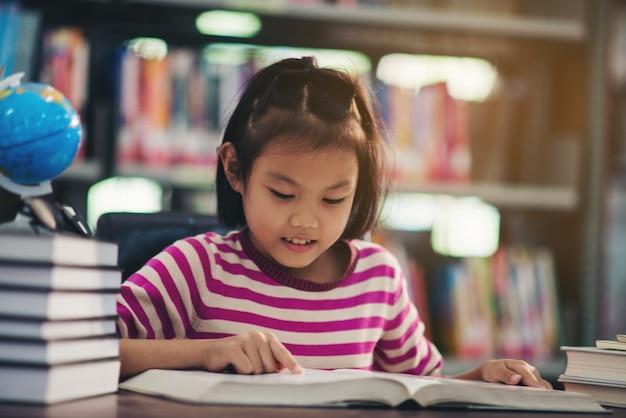 Porträt eines studentenkindermädchens, das an der bibliothek studiert Kostenlose Fotos