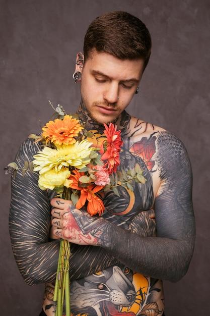 Porträt eines tätowierten hippie-mannes, der in der hand blumenstrauß gegen grauen hintergrund hält Kostenlose Fotos