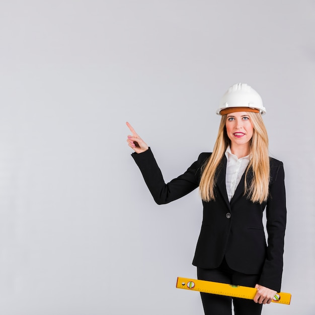 Porträt eines tragenden hardhats des jungen weiblichen architekten, der ihren finger gegen grauen hintergrund zeigt Kostenlose Fotos