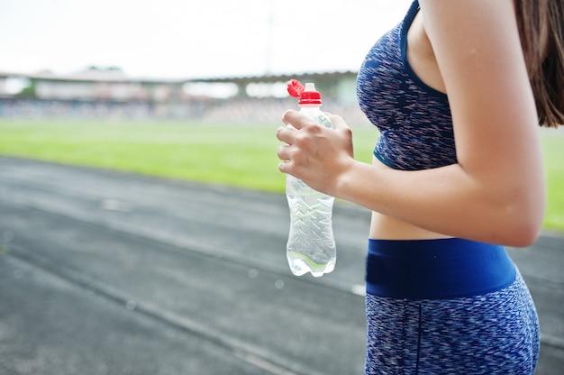 Porträt eines trinkwassers der sitzfrau, nachdem in das stadion gelaufen worden ist. Premium Fotos