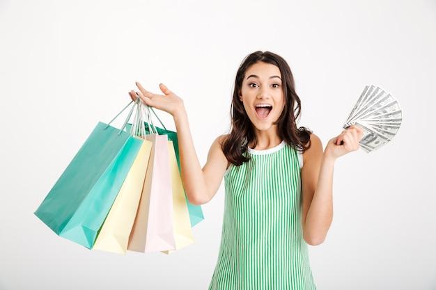 Porträt eines überraschten mädchens im kleid, das einkaufstaschen hält Kostenlose Fotos