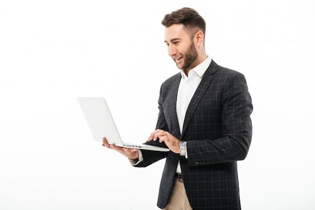 Porträt eines überzeugten bärtigen mannes, der laptop-computer verwendet Kostenlose Fotos
