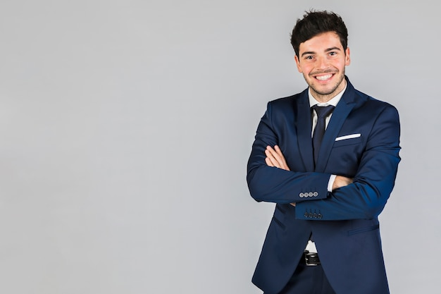Porträt eines überzeugten jungen geschäftsmannes mit seinem arm kreuzte stellung gegen grauen hintergrund Kostenlose Fotos