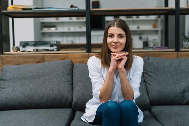 Porträt eines weiblichen arztes, der auf grauem sofa mit der hand umklammert sitzt Kostenlose Fotos