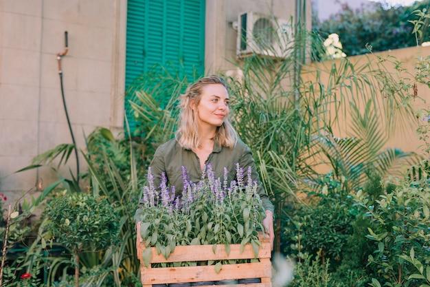 Porträt eines weiblichen gärtners, der hölzerne kiste lavendelblumen hält Kostenlose Fotos