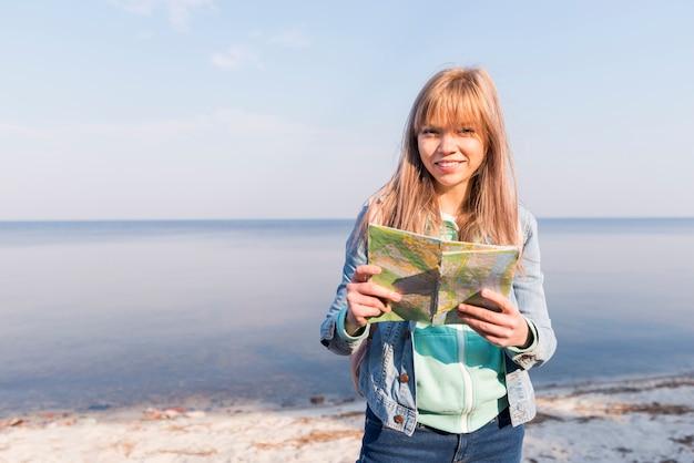 Porträt eines weiblichen reisenden, der die karte in der hand betrachtet die kamera steht nahe dem meer hält Kostenlose Fotos