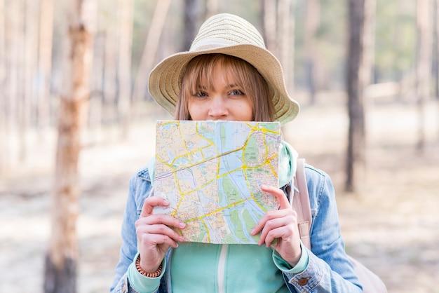 Porträt eines weiblichen reisenden, der karte vor ihrem mund betrachtet kamera hält Kostenlose Fotos