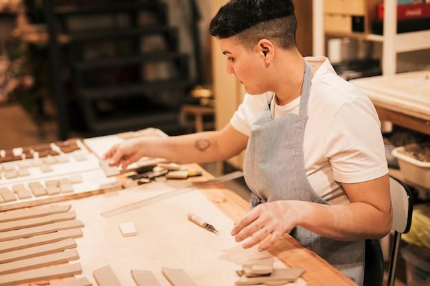 Porträt eines weiblichen töpfers, der die lehmfliesen auf dem holztisch in der werkstatt vereinbart Kostenlose Fotos