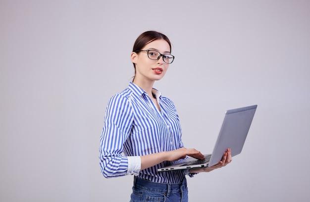 Porträt eines weiblichen verwalters in einem gestreiften weiß-blauen hemd mit gläsern und einem laptop auf grau. mitarbeiterin des jahres, business lady. kopieren sie platz. Premium Fotos
