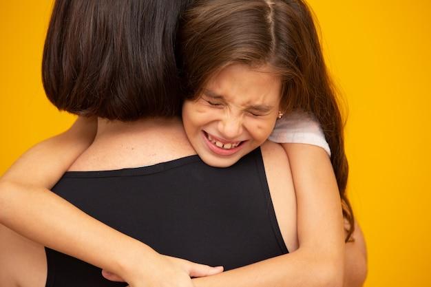 Porträt eines weinenden kleinen mädchens, das von ihrer mutter gehalten wird Premium Fotos